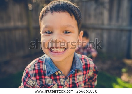 Cute 4 year old mixed race Asian Caucasian boy plays in the backyard of his suburban home. Filtered effects - stock photo