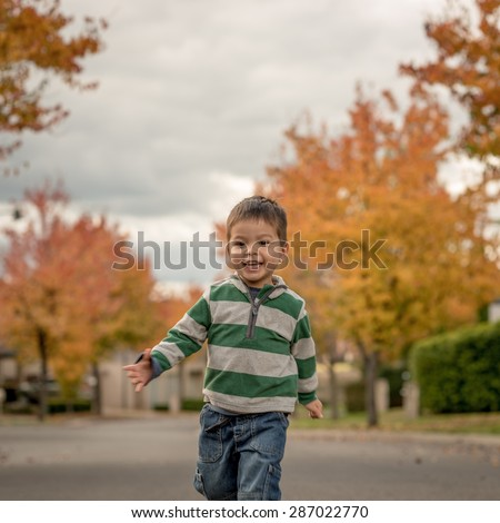 Cute 2 year old mixed race Asian Caucasian boy runs up his quiet suburban street in his neighborhood. Autumn (Fall) trees lining the street in the background. Square crop and Instagram style. - stock photo