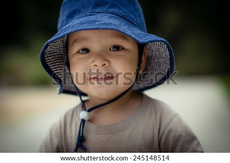 Cute 2 year old mixed race Asian Caucasian boy wearing a blue hat outside smiles sweetly looking at the camera - stock photo