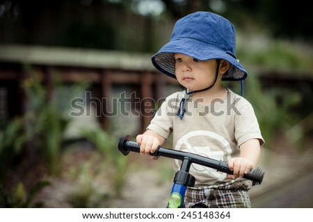 Cute 2 year old mixed race Asian Caucasian boy wearing a blue hat rides his balance bike outside in the summer sun