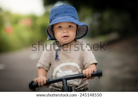 Cute 2 year old mixed race Asian Caucasian boy wearing a blue hat rides his balance bike outside in the summer sun - stock photo