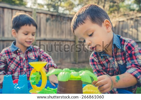 Cute 2 year old mixed race Asian Caucasian brothers play happily with a water toy in their suburban house backyard. Filtered effects - stock photo