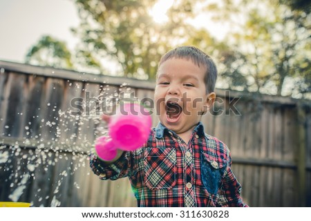 Cute 2 year old mixed race Asian Thai Caucasian boy plays excitedly with water in his Australian suburban home backyard - stock photo
