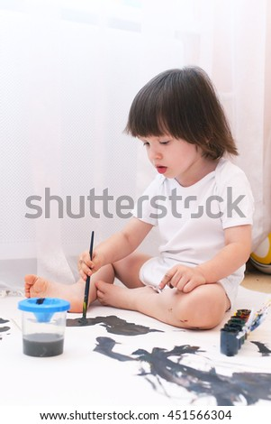 Cute 2 years boy with brush and gouache paints at home