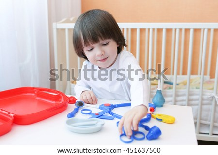Cute 2 years child plays doctor at home