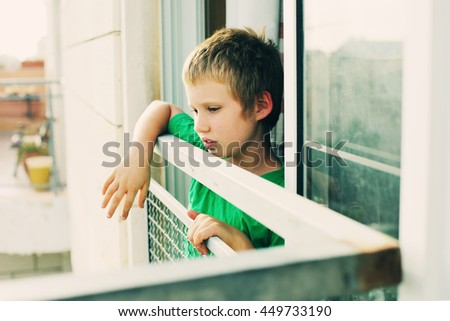 Cute 8 years old autustic boy looking at the street