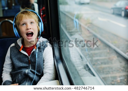 Cute 8 years old boy looking through the window in the train