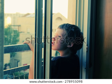 Cute 7 years old boy looks out the window to the street