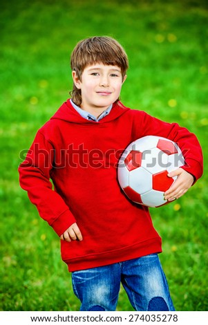 Cute 7 years old boy playing with a ball outdoor. Summer day.  - stock photo