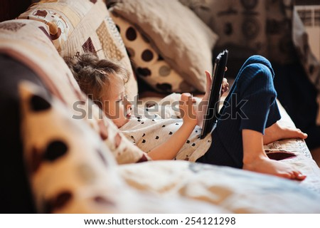 cute 5 years old child girl playing tablet at home on the sofa
