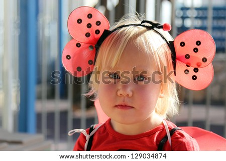 cute 2 years old girl dressed as a ladybug - stock photo