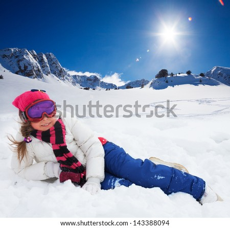 Cute 10 years old girl in ski mask and bright snow clothes laying in snow with mountains on background