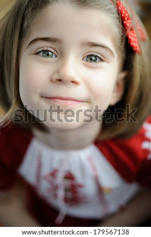 Cute 5 years old girl look straight at you and smiles, dressed in a traditional Romanian dress - stock photo