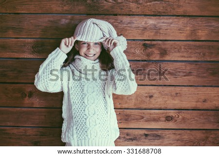 Cute 9 years old girl wearing knitted autumn or winter clothing posing over wooden background - stock photo