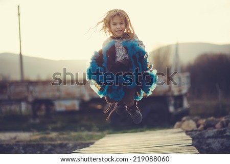 Cute 5 years old girl wearing tutu skirt jumping over sunset sunlight in rustic scene - stock photo