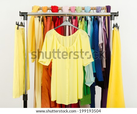 Cute yellow blouse and skirts displayed on a rack. Wardrobe with colorful summer clothes and accessories.