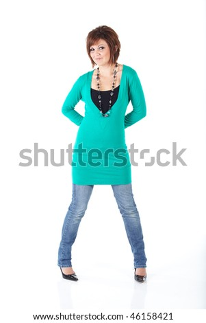 Cute young adult caucasian woman wearing a Turquoise top and a beaded necklace with blue jeans and with short brunette hair on a white background. Not Isolated