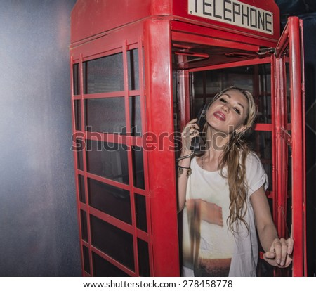 Cute young adult Girl inside a traditional English red telephone booth metal box look at camera Sexy caucasian woman wear stylish white shirt with the handset in hand Female opens the door - stock photo