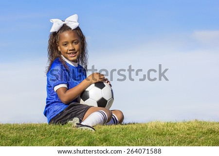 Cute, young african american girl soccer player holding a ball sitting on a grass field - stock photo