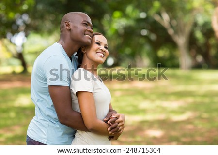 cute young african couple daydreaming in forest - stock photo