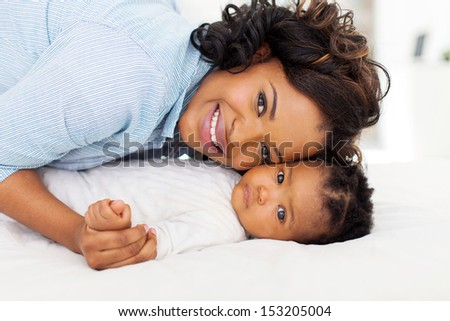 cute young african mother and her baby lying on bed - stock photo