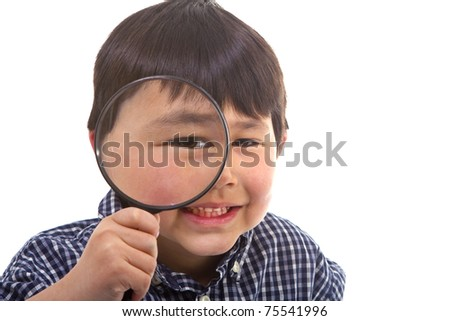 Cute young asian boy looking through a large magnifying glass isolated on white background