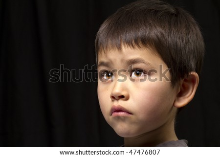 Cute young asian boy looking up on dark background
