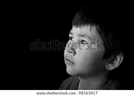 Cute young asian boy looking up with serious look on black background in black and white