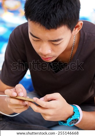 cute young asian boy with black short hairs wearing dark casual brown gray t-shirt blue sport watch sitting on the floor concentration on playing game and reading message on mobile handy smart phone - stock photo