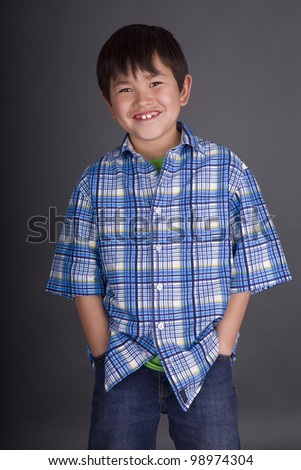 Cute young asian boy with great smile and wearing casual clothes on a grey background