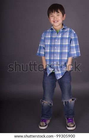 Cute young asian boy with great smile and wearing casual clothes on a grey background - stock photo