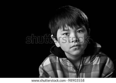 Cute young asian boy with serious look on black background in black and white - stock photo