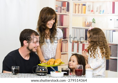 Cute young attractive family with two preschooler girls eating breakfast - stock photo