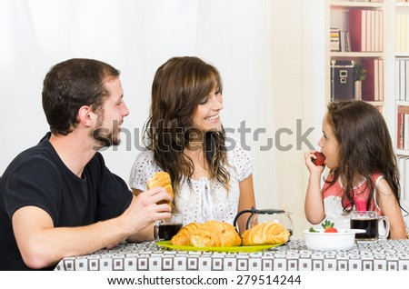 Cute young attractive happy family with preschooler girl eating breakfast - stock photo