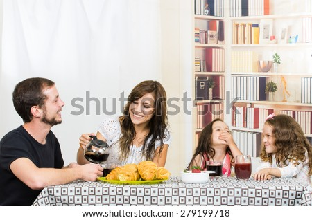 Cute young attractive happy family with two preschooler girls eating breakfast - stock photo