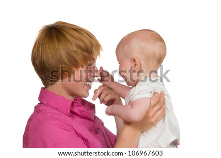 Cute young baby looking away from the camera gently touching the nose of its happy smiling mother