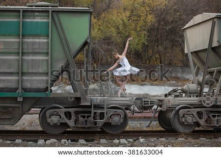 Cute young ballerina making a pose while standing on a freight wagon's platform between two wagons on railway rails. She is wearing a white tutu with ballet shoes. There are many trees behind her - stock photo