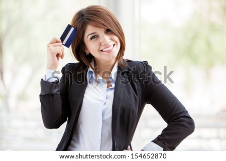 Cute young bank representative on a suit holding a business card in her hand and smiling