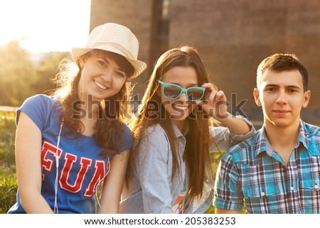 Cute young beautiful teens sitting in city near university after studying and having fun together laughing and smiling