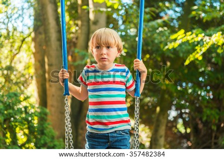 Cute young blond boy having fun on a swing on a nice summer day, wearing stipe tee - stock photo
