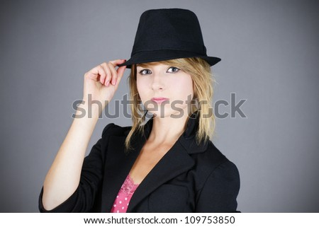 Cute young blond teenager girl model wearing a black felt hat and coat, studio shot over grey background.