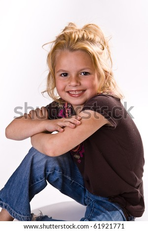 Cute young blond with her arms crossed wearing jeans and a brown shirt.