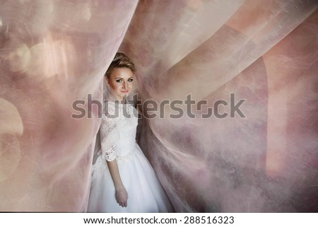 cute young blonde bride posing under long curtains  on a background of room