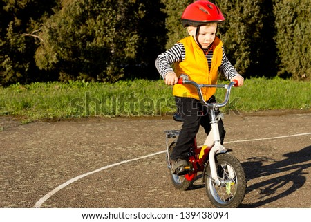 Cute young boy dressed in a colourful red safety helmet and orange high visibility jacket practising riding his bike on a quiet country lane - stock photo