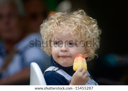 cute young boy eating ice cream in summer - stock photo