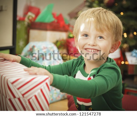 Cute Young Boy Enjoying Christmas Morning Near The Tree. - stock photo