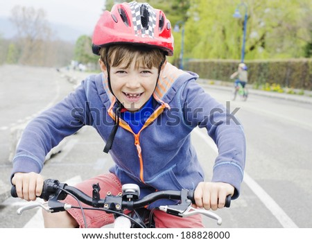 Cute young boy gripping the handle bars of his bike - stock photo