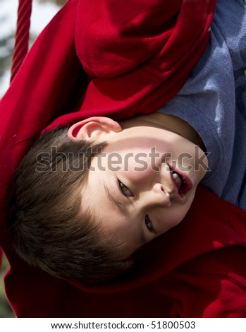 Cute young boy hanging upside down on a playground structure