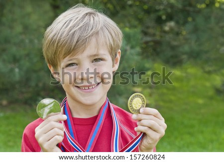 Cute, young boy holding up gold medals - stock photo