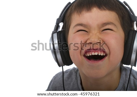 cute young boy listening to music and laughing